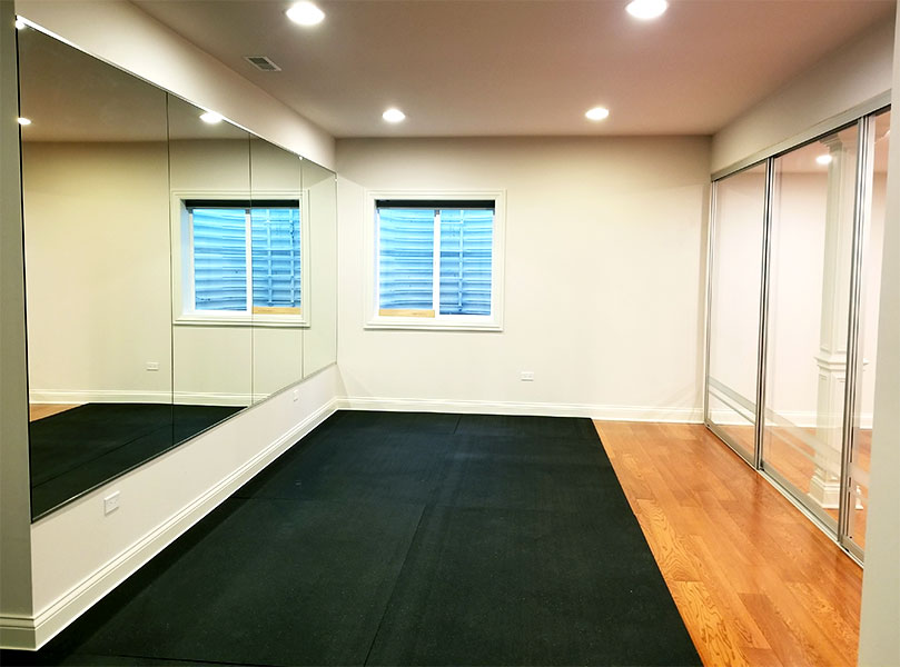 basement home gym with large wall mirrors and clear sliding glass room dividers