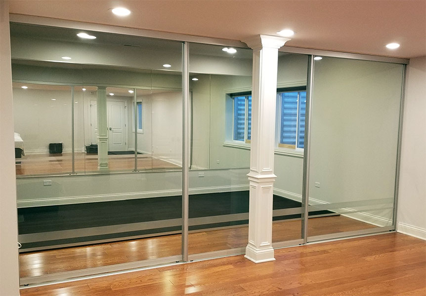 basement home fitness area with etched glass sliding room dividers or bypass doors